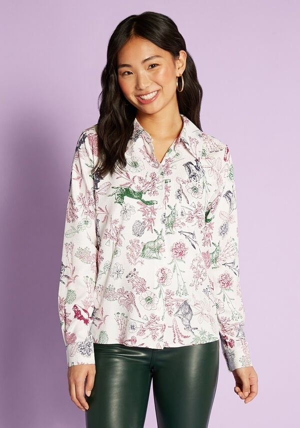 model wearing the white shirt with red, green, and navy flower and animal print