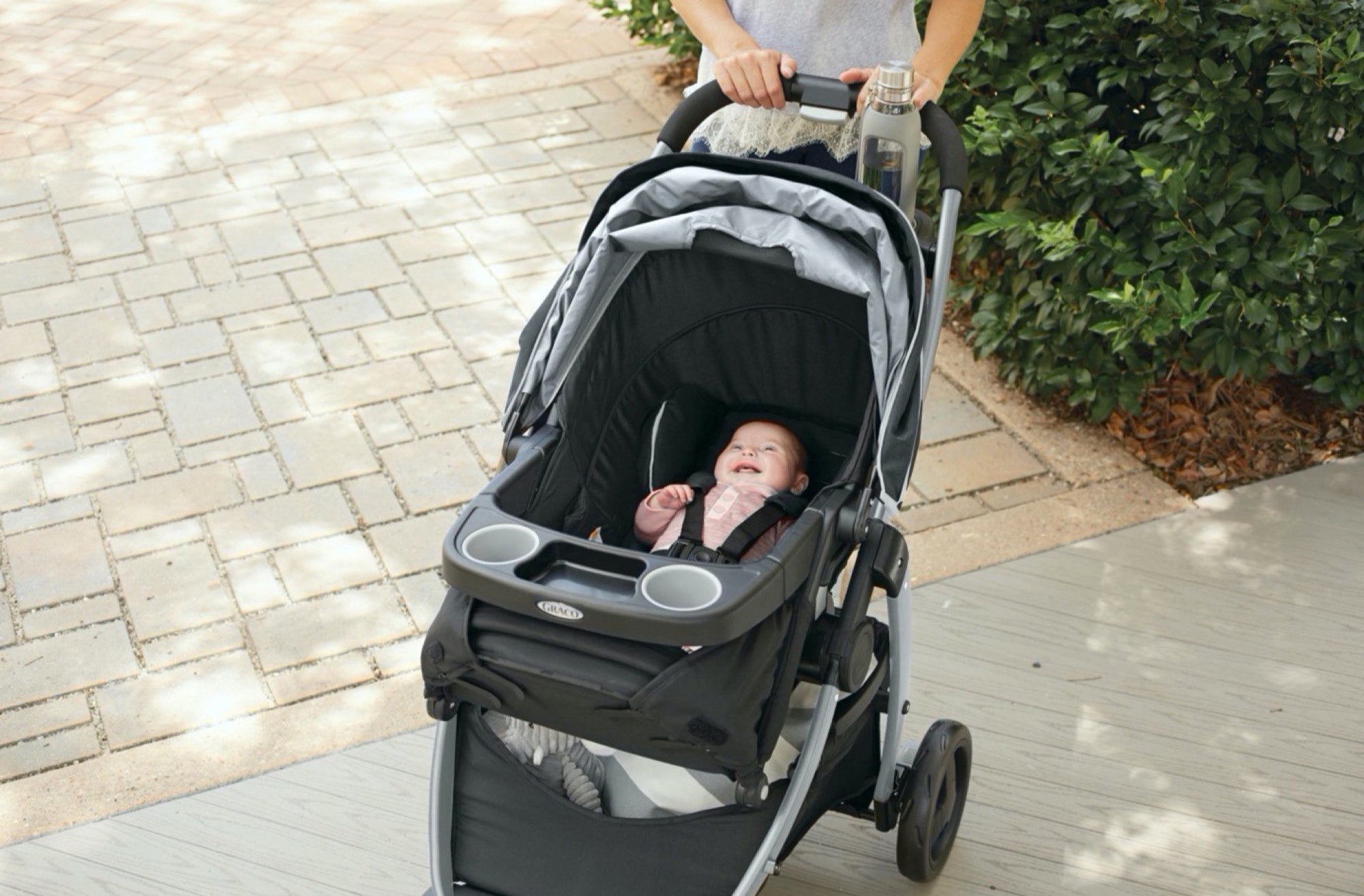baby in a stroller as a parent pushes the stroller
