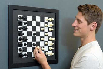 Model playing the magnetic chessboard attached to the wall