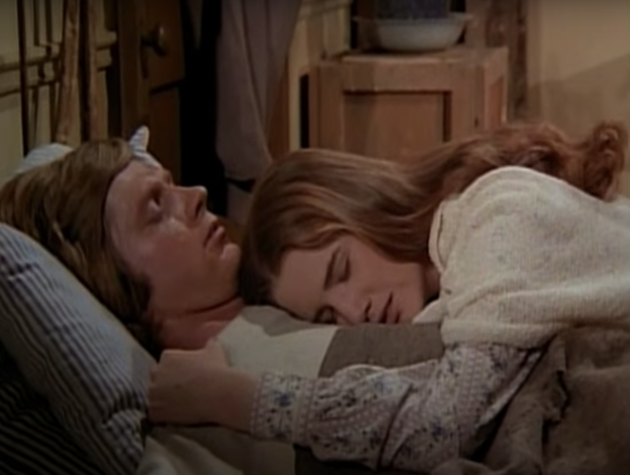Melissa Gilbert lying on Dean Butler's chest in a scene from the show