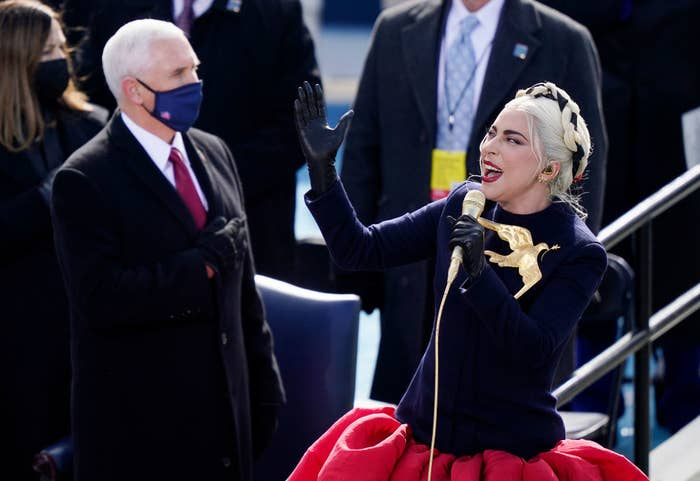 Lady Gaga belts out the National Anthem in a voluminous skirt and coat top featuring a dove carrying an olive branch