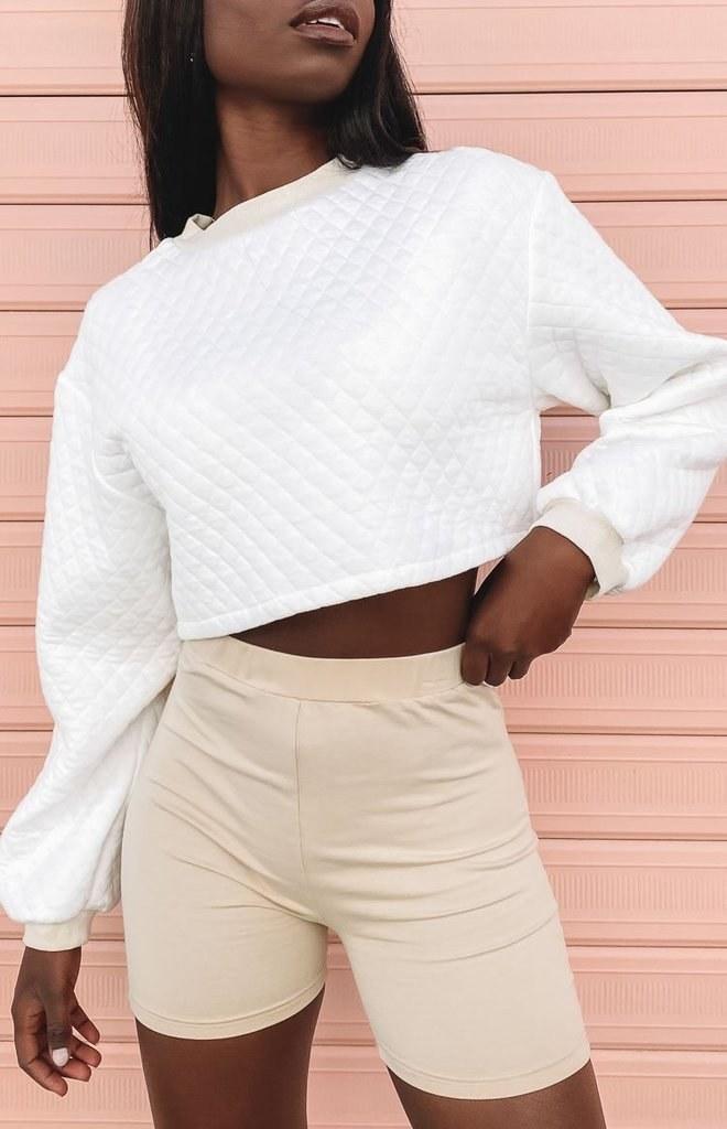 A model wearing the white sweatshirt