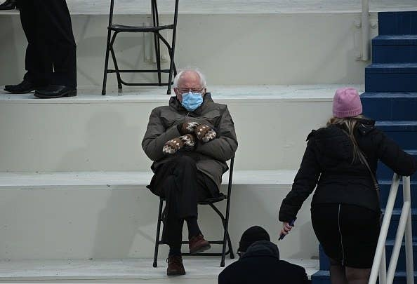 Bernie Sanders sitting at a safe social distance from other guests with his legs and mitten-covered hands crossed