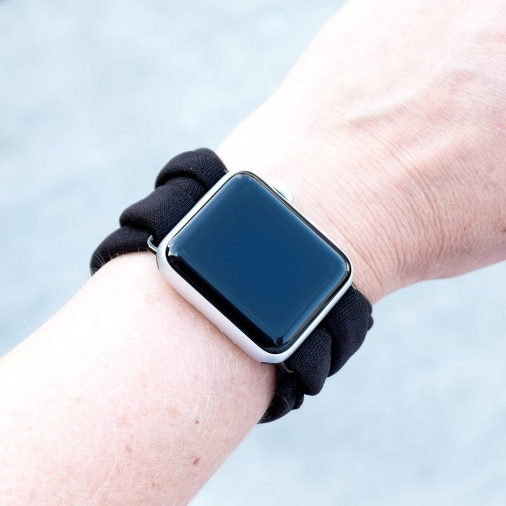 A model wearing an Apple Watch with a soft multiloop black band