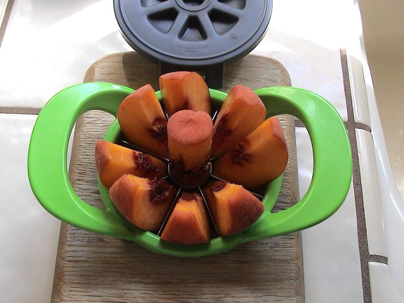 Reviewer's apple slicer in use on peach