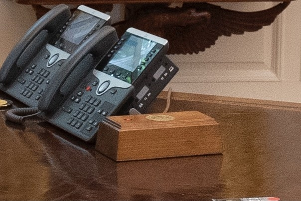 The red button inlayed in wood laid next to two landline phones