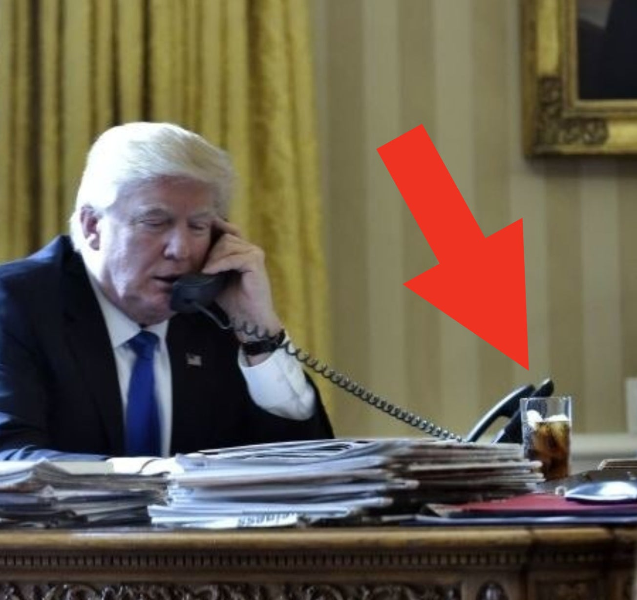 Trump on the phone with a tall glass of Diet Coke on his desk next to stacks of papers