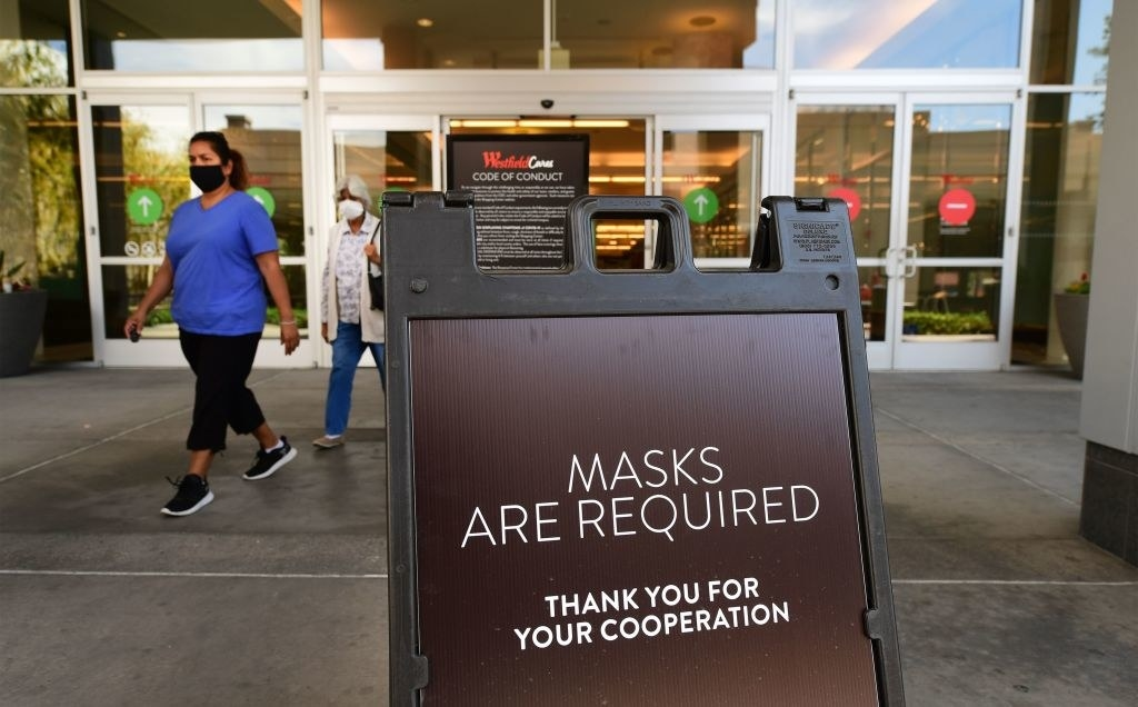 """a sign outside a mall that says """"masks are required"""""""