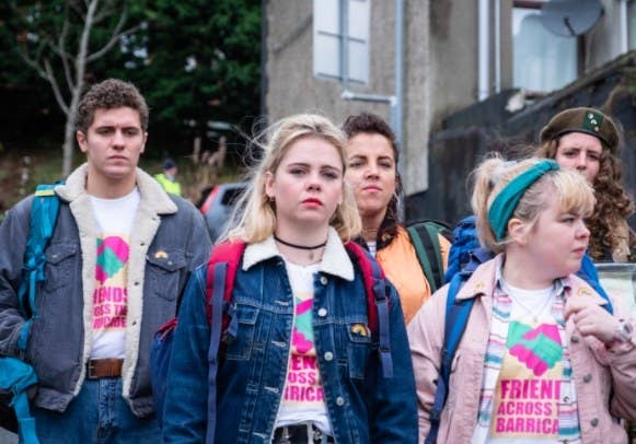 """The cast of Derry Girls walk down the street, wearing """"friends across barricades"""" tshirts and jackets"""