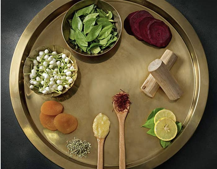 Brass thali with herbs, fruit, flowers, ghee and saffron