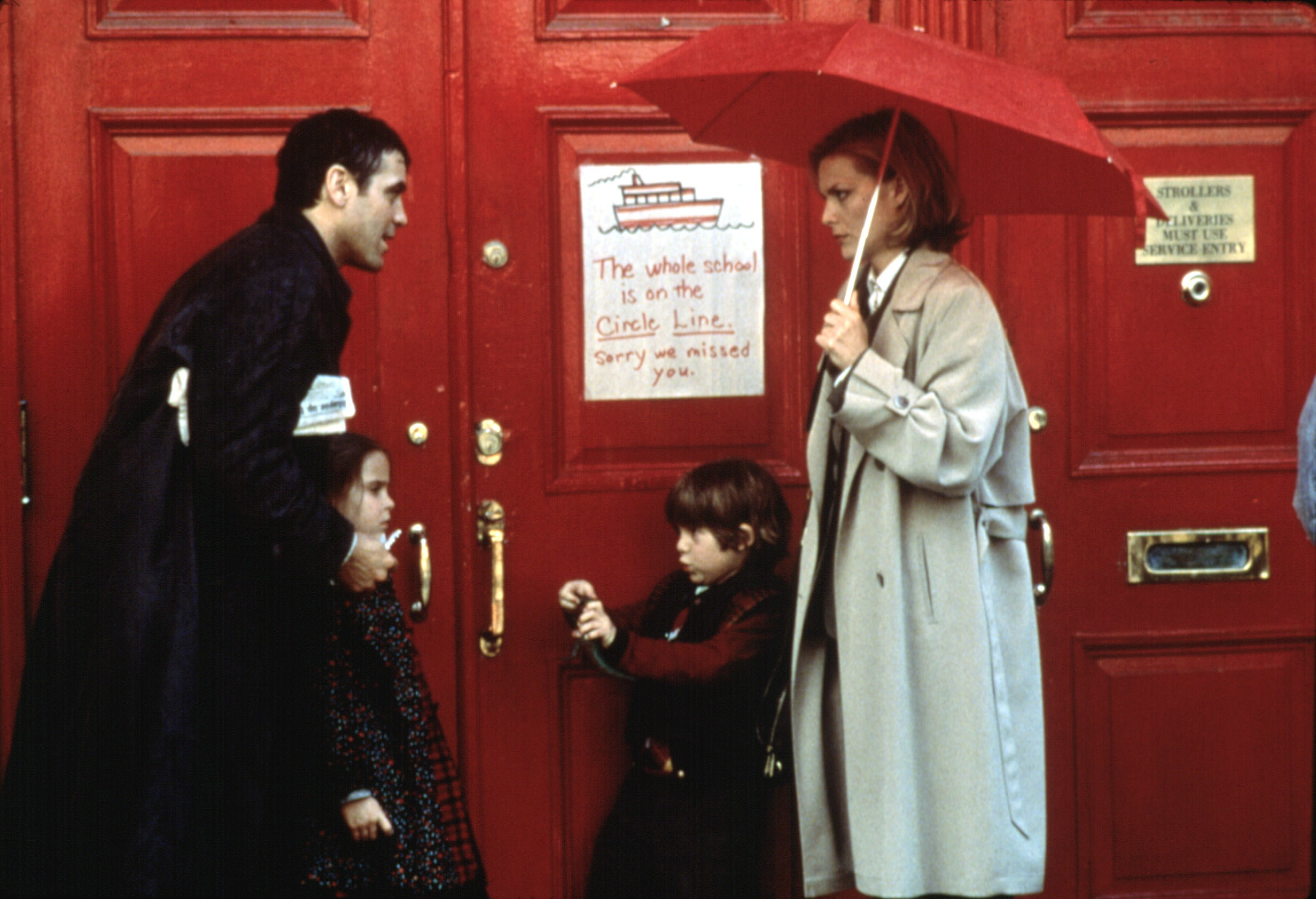 "George Clooney, Mae Whitman, Alex D. Linz, Michelle Pfeiffer standing in the rain outside of a building with a sign that says ""The whole school is on the Circle Line, Sorry We Missed You"""