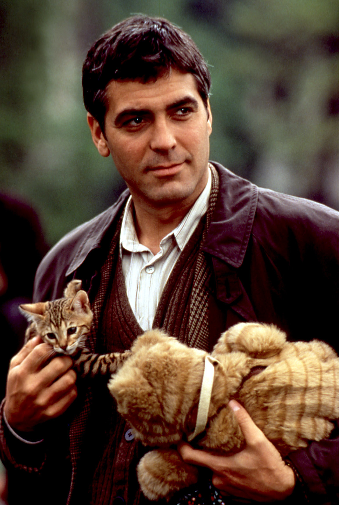 George Clooney holding a cat and a stuffed animal in One Fine Day