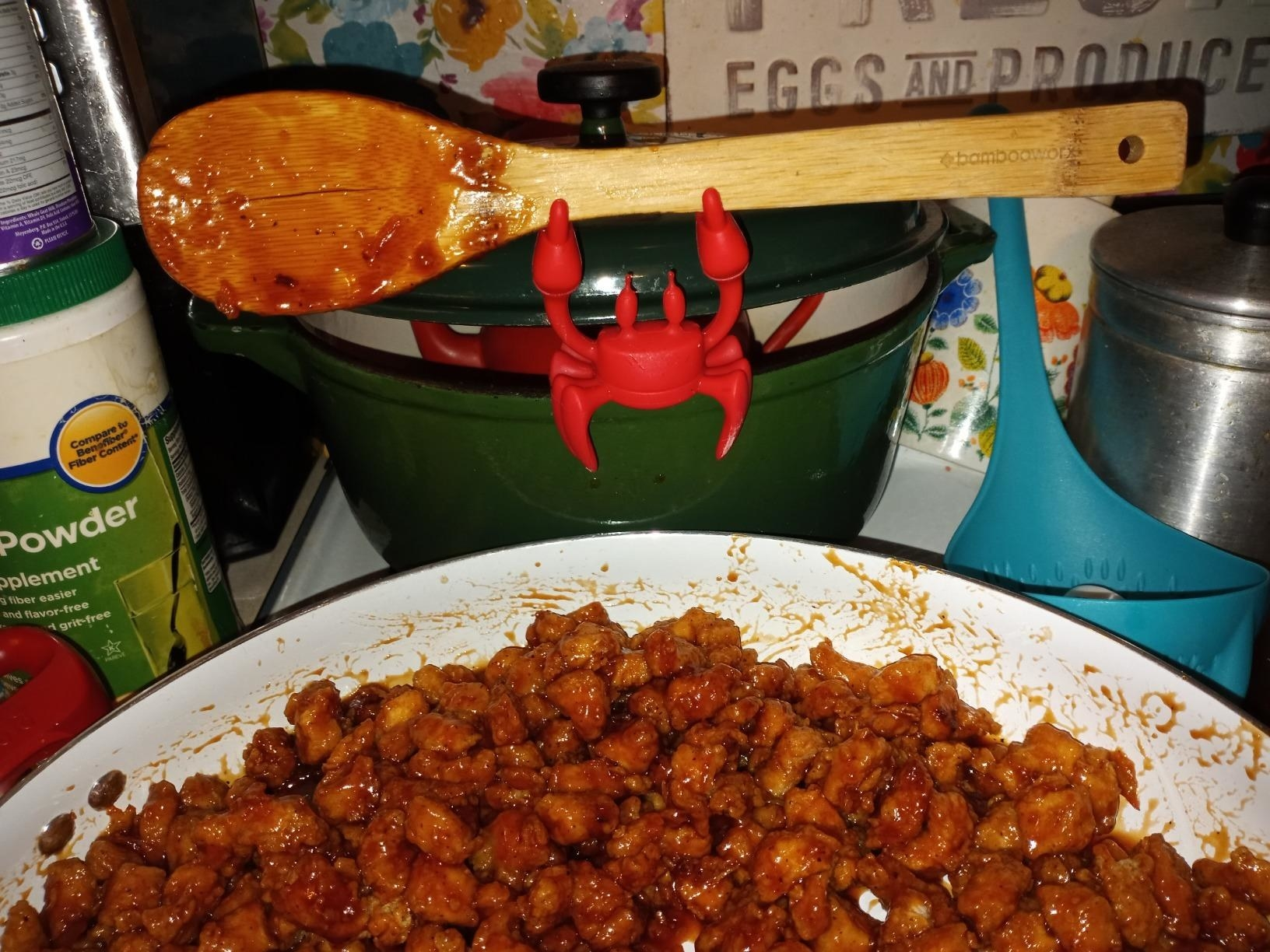 reviewer photo showing the crab spoon holder attached to a pot, holding a wooden spoon while also propping the lid open for steam