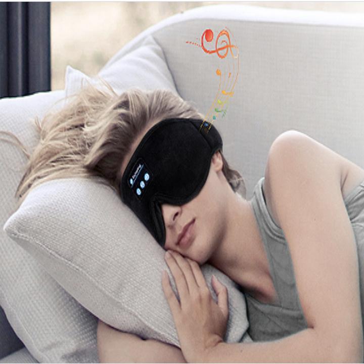 Model wearing a black eye mask and sleeping