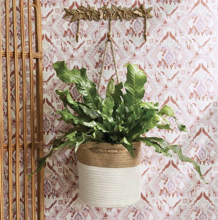 A cream and beige hanging basket with a plant in it