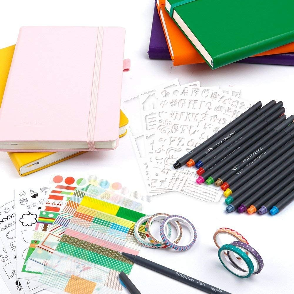 the complete dotted journal kit with several journals of different colors laid out on a table