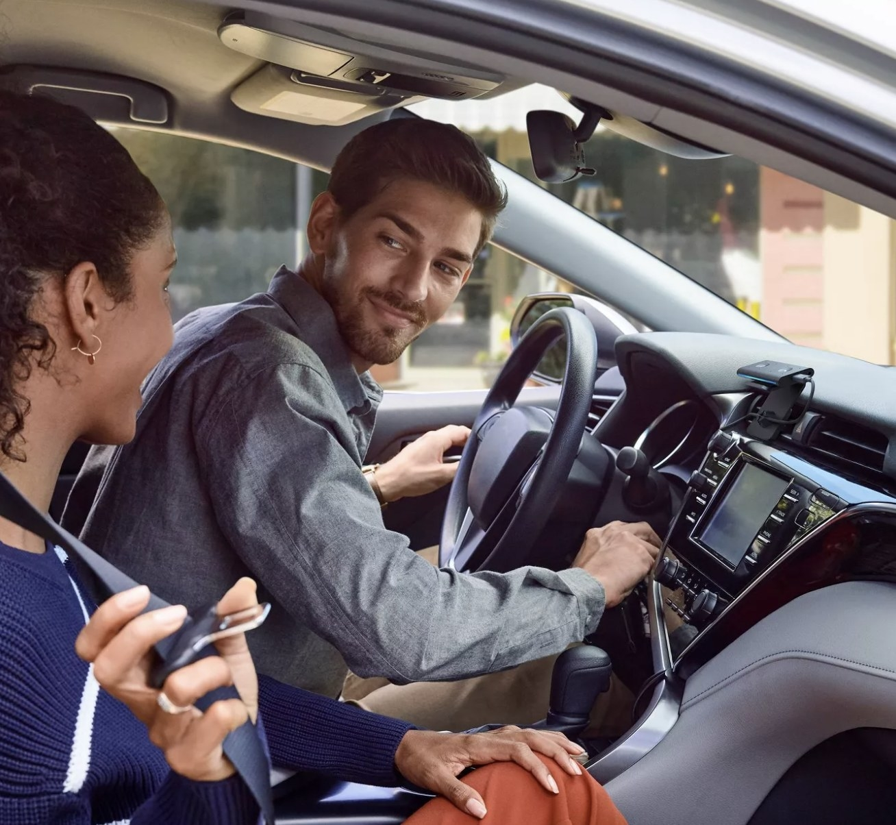 Two people in a car with an Amazon Echo Auto clipped to the car vents