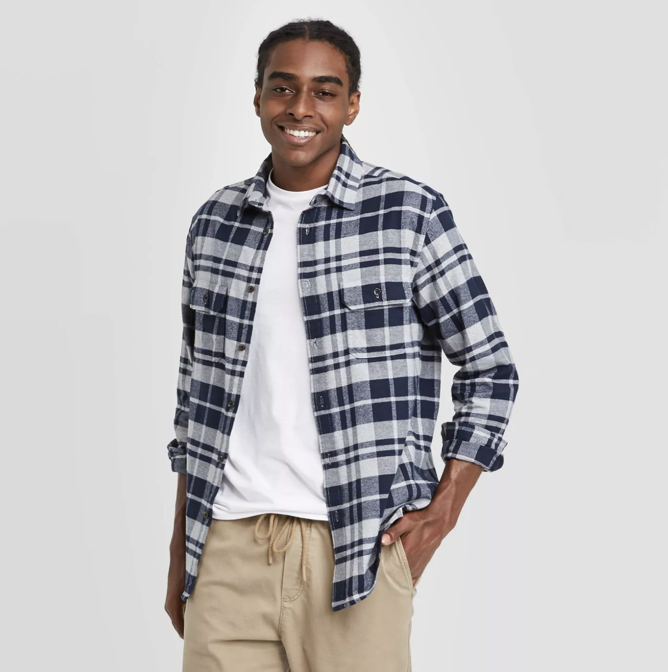 Model is wearing a black and white flannel shirt over a white tee and khaki pants