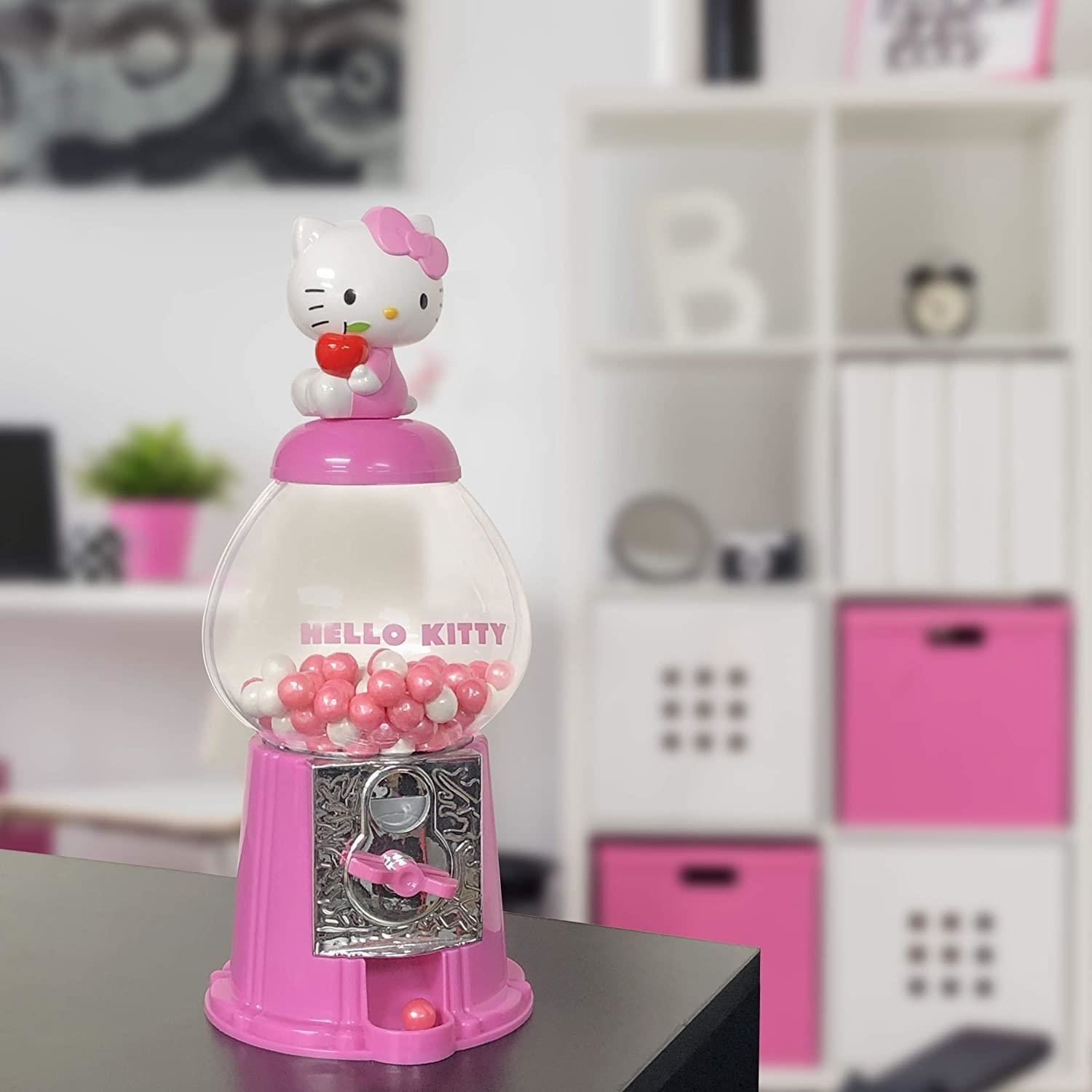 pink mini gumball machine with hello kitty holding an apple on top
