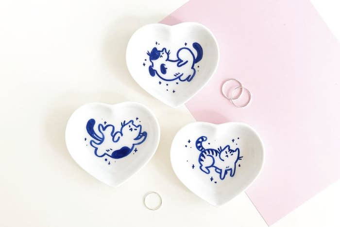 three heart shaped dishes with a blue illustrated cat on each