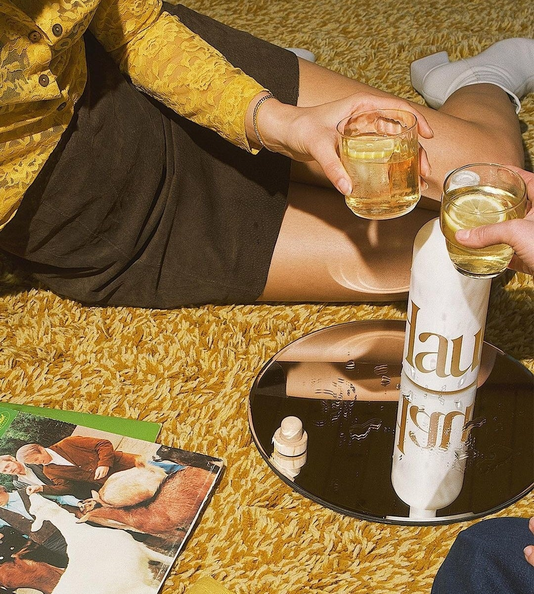 A tray with a bottle of Haus with a model holding a glass sitting on the floor