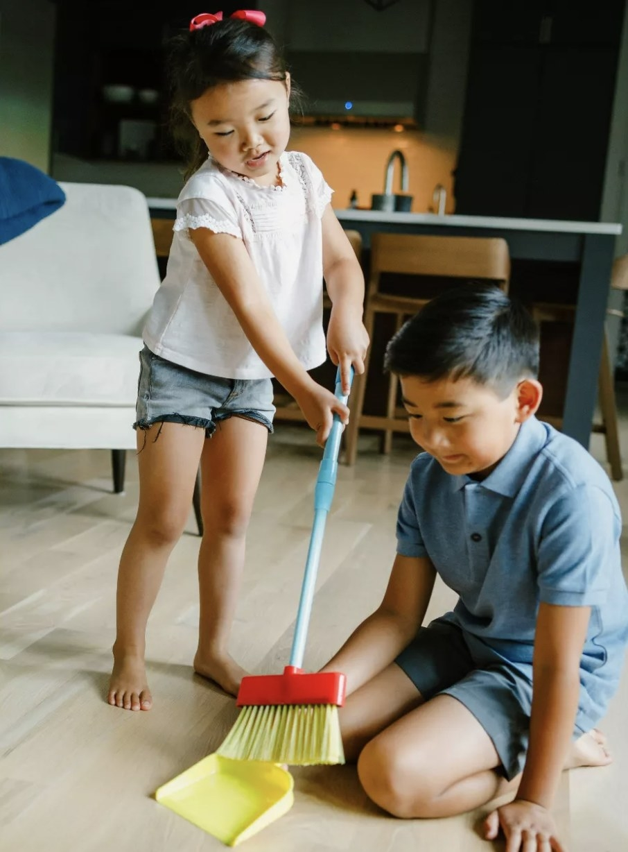 Two young people sweeping the floor