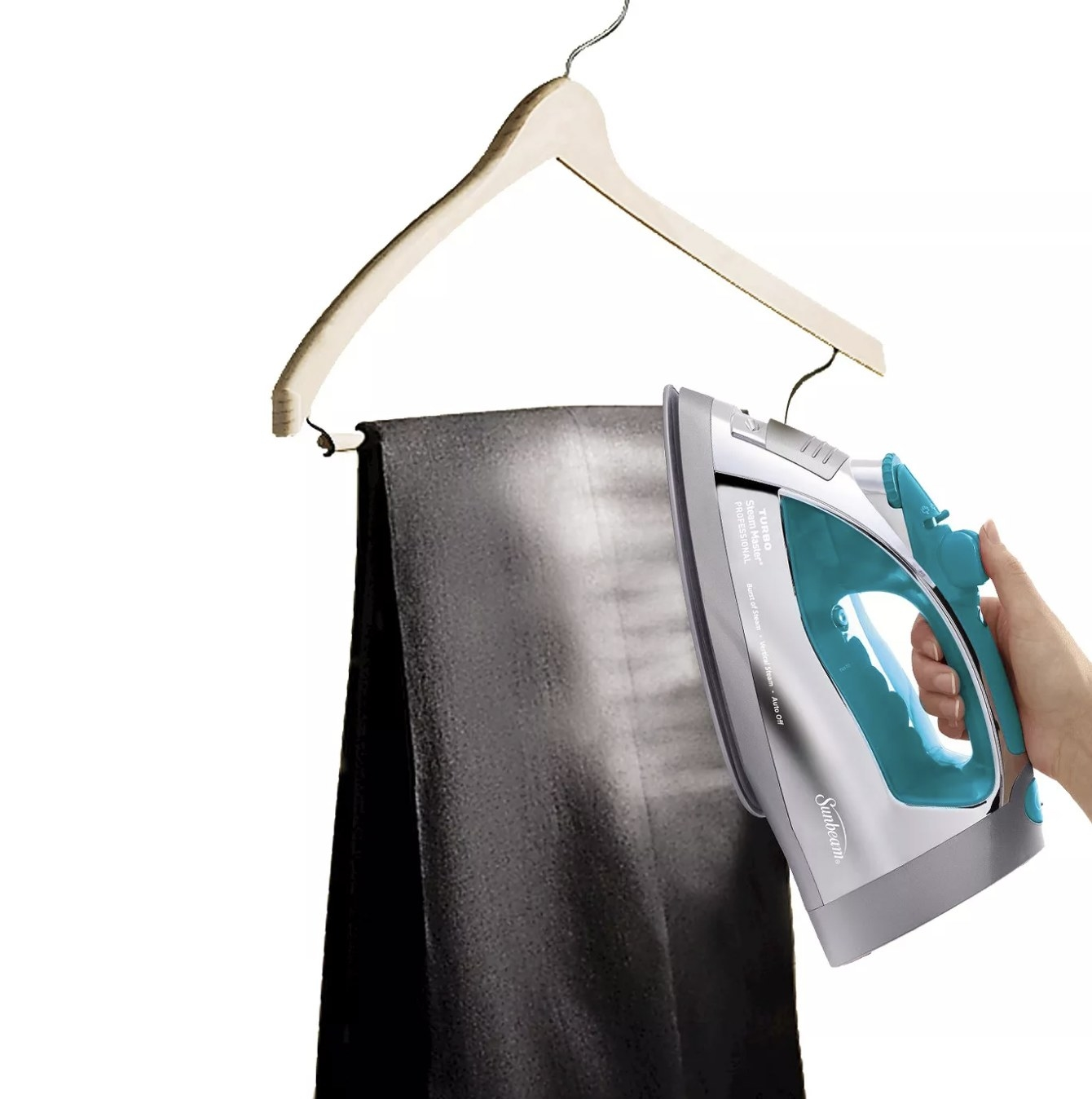 A person is steaming a pair of black pants with an iron