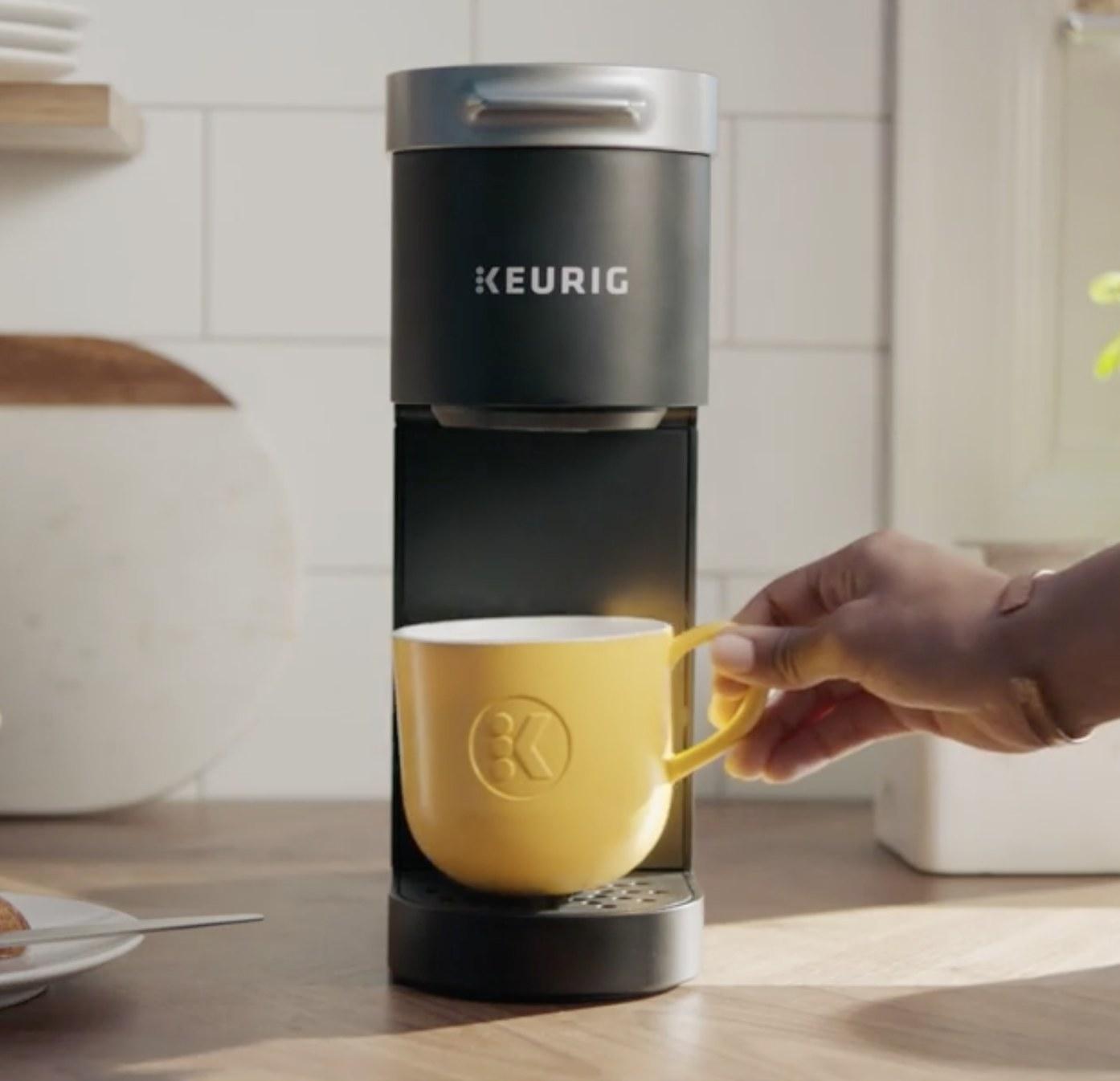 Person is placing a yellow mug on a black Keurig mini coffee maker
