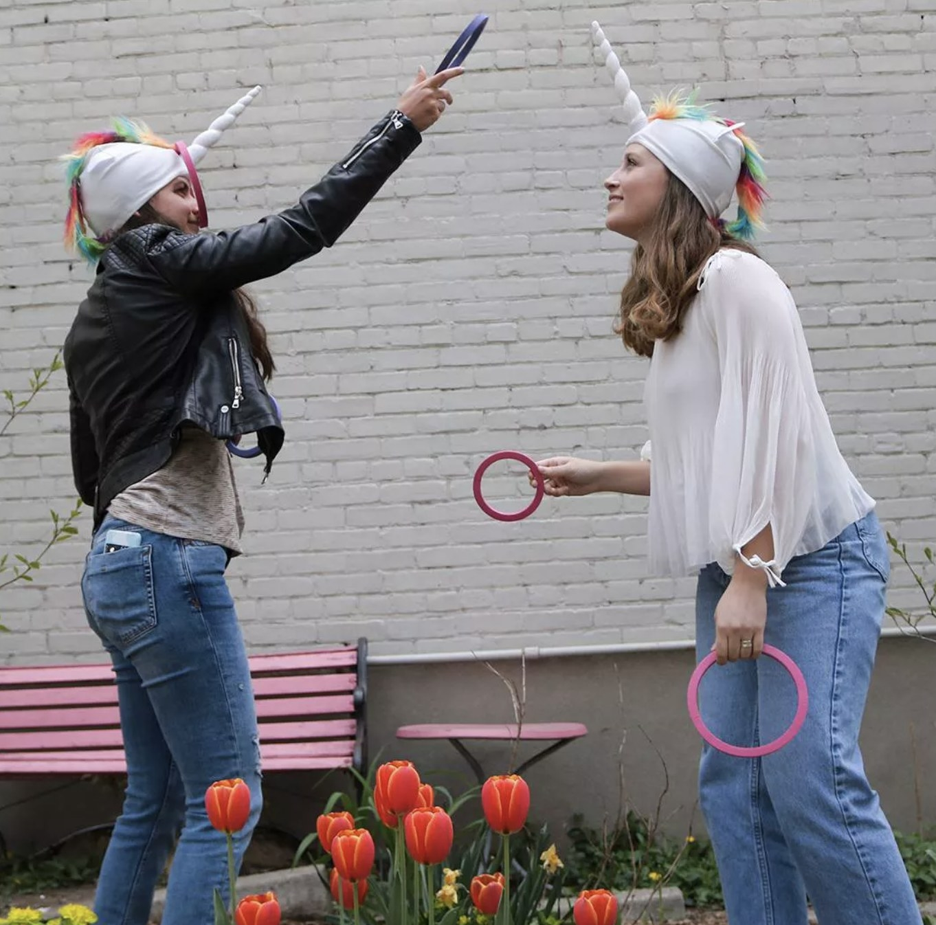 Two people playing the unicorn ring toss game