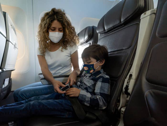 A woman buckling a child's airplane seatbelt