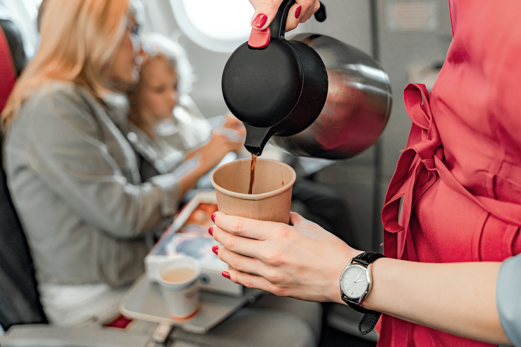 A flight attendant pouring coffee next to a woman and a child