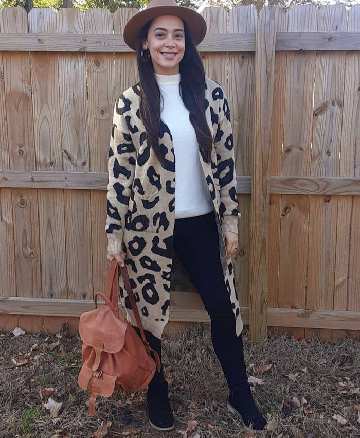 reviewer wearing the leopard print long open front cardigan with pockets