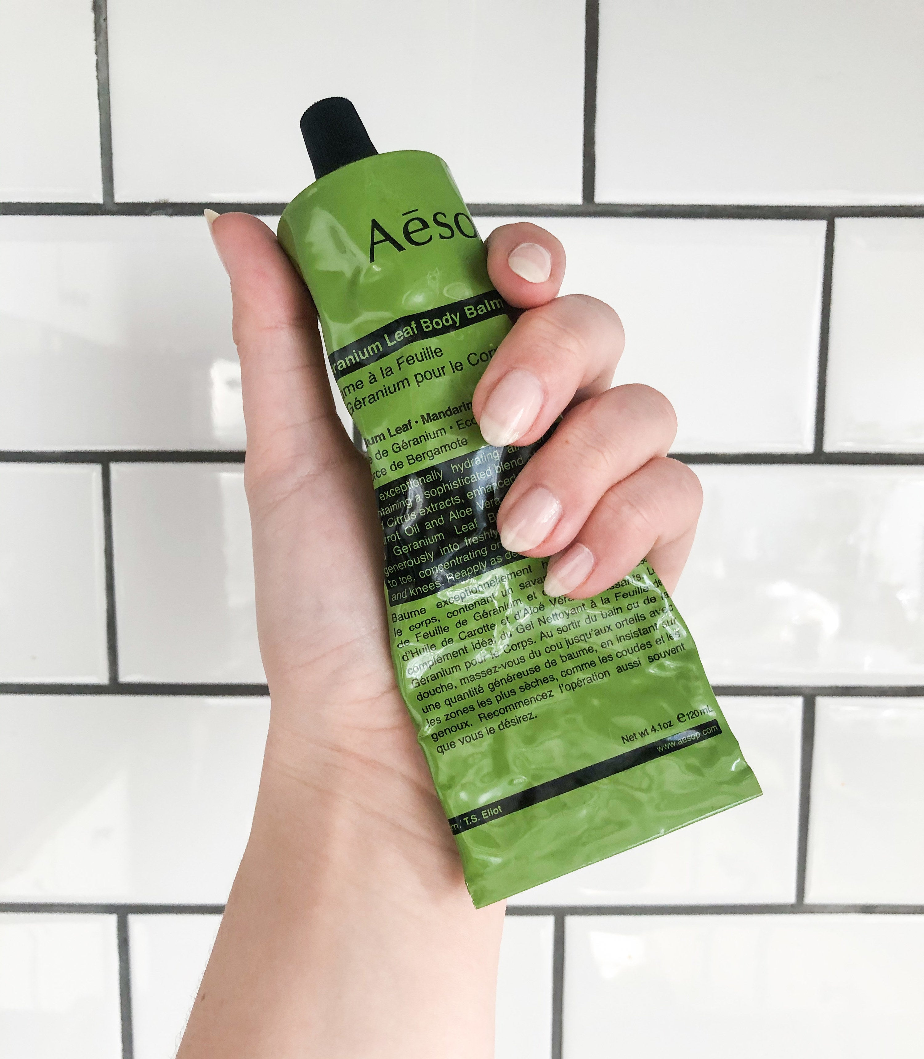 Victoria holding up a tube of the cream against a subway tile backsplash