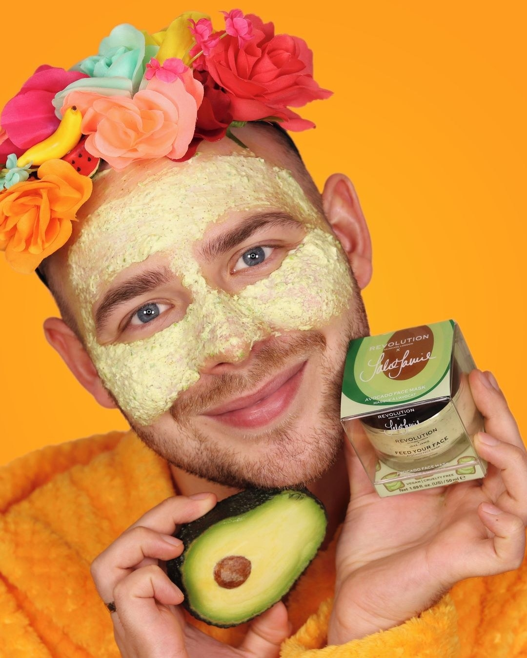 A person with the avocado mask on their face, holding an avocado and the mask while looking into the camera
