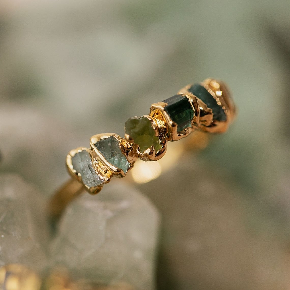 Band ring in gold with several small rough stones gilded in gold all in a line