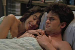 Janet and Chandler from friends in bed together with Janet laughing and smiling and Chandler looking away, freaked out