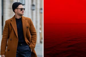 A man walks down the street wearing a beanie and sunglasses and a red hued fog falls over a body of water.