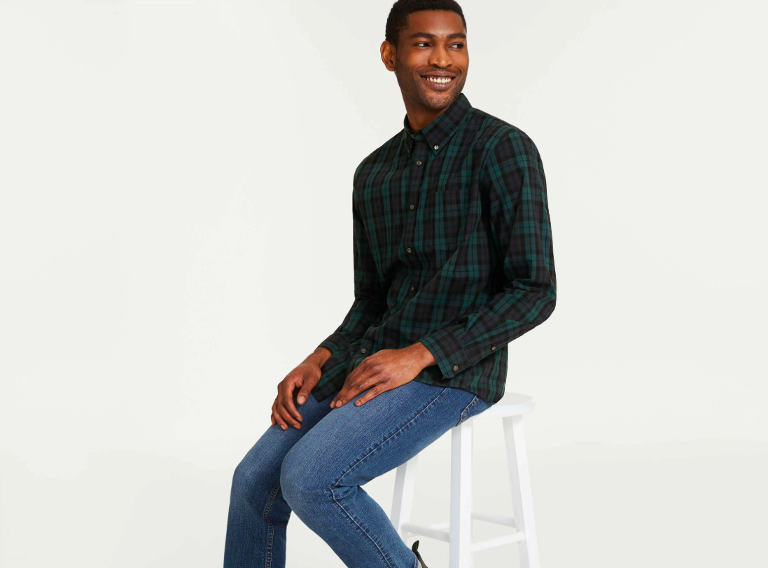 A person sitting on a stool wearing a button up shirt and jeans