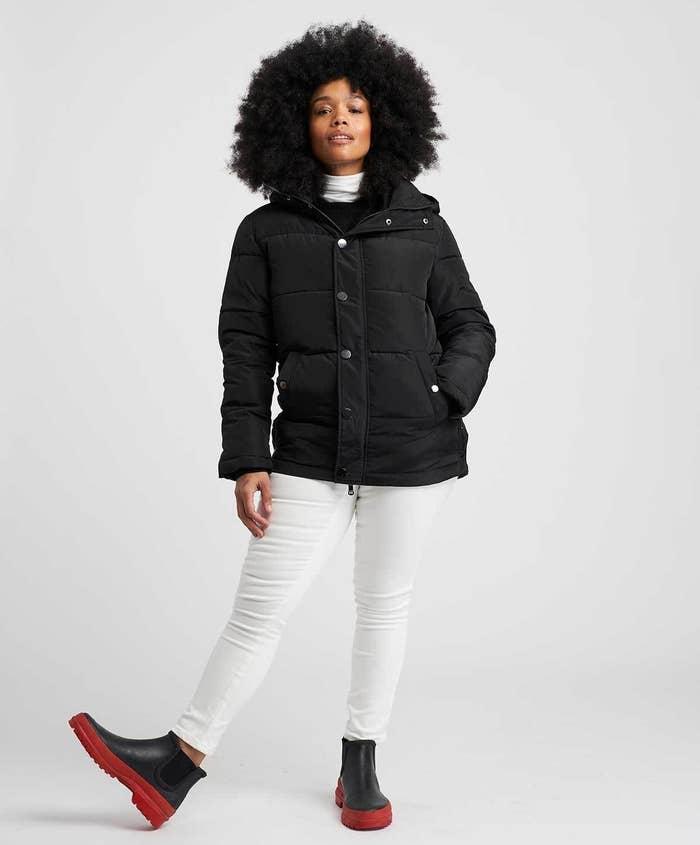 model in black short hooded puffer coat