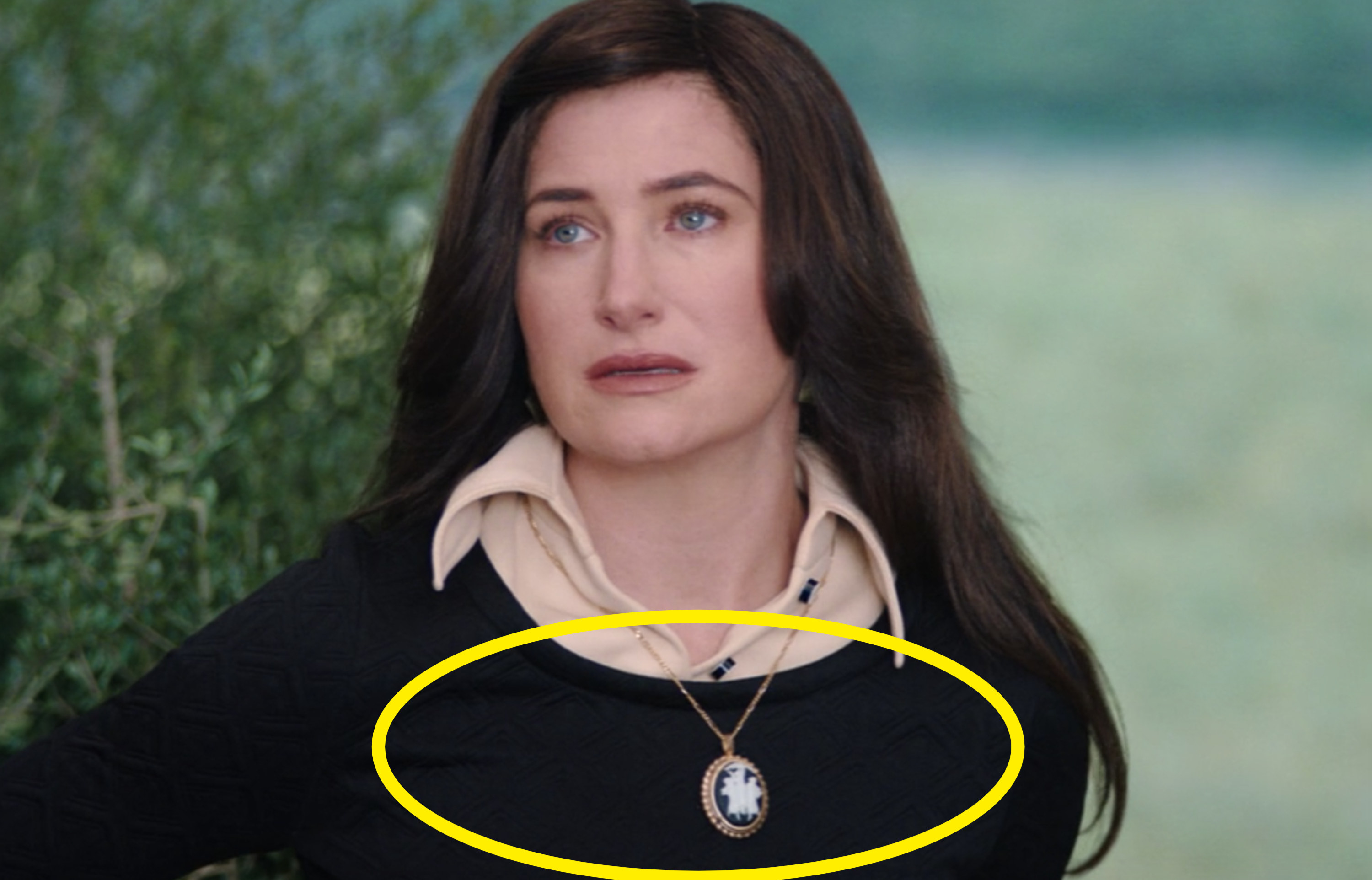 Agnes wearing a black sweater with a large broach on a necklace