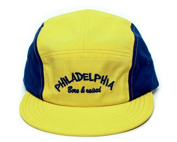"""yellow and blue baseball-style cap that says """"Philadelphia born and raised"""" on the front"""