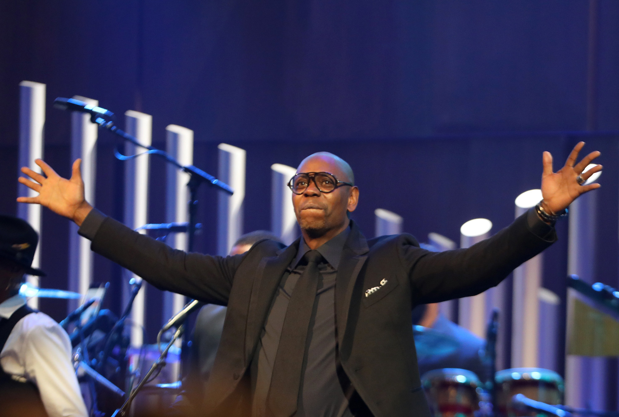 Dave Chappelle raises his arms during the Mark Twain award show at the Kennedy Center