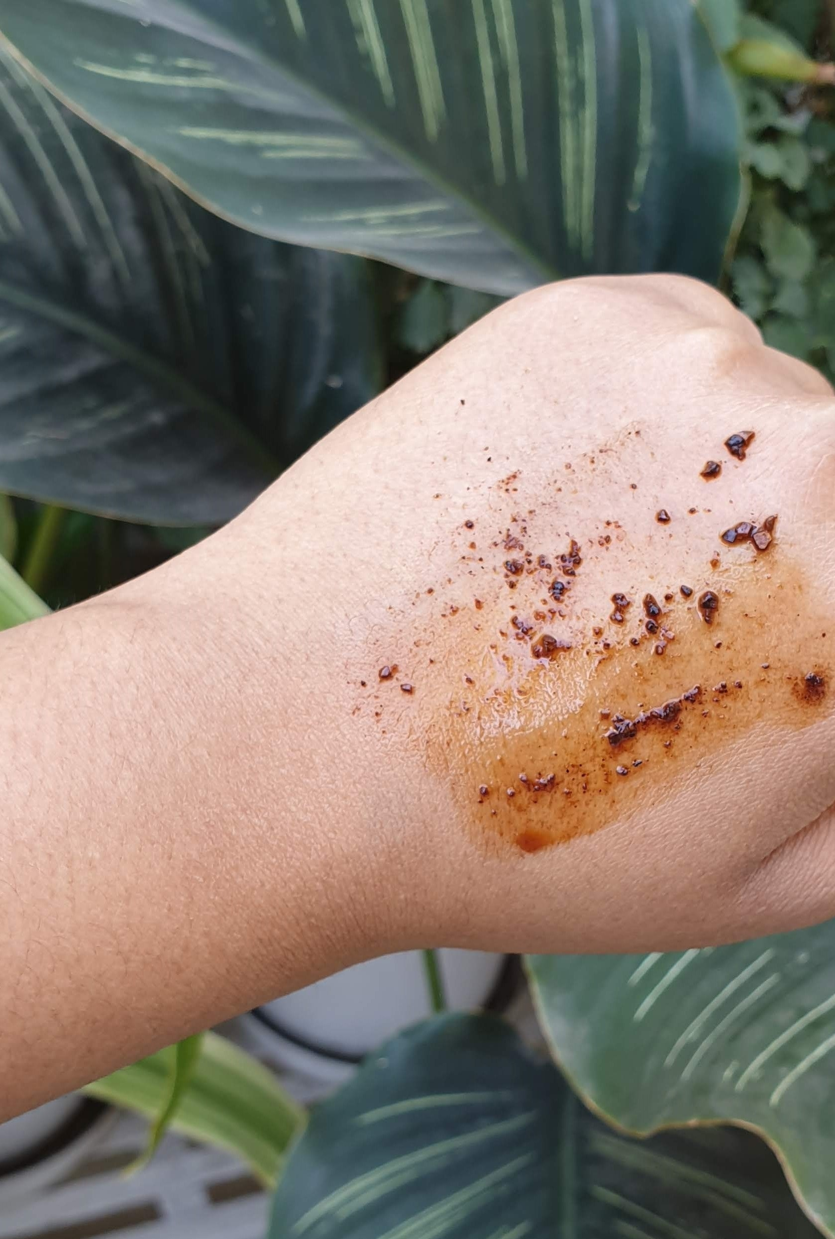 The coffee body scrub pictured on my hand, mixed with water.