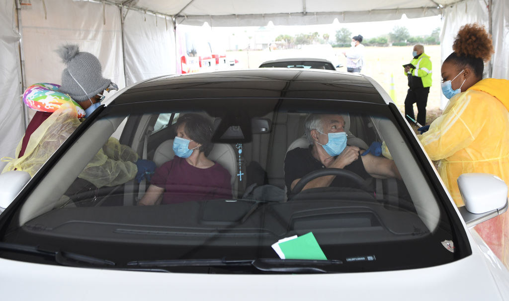 Two older people receive COVID-19 shots while seated in their car