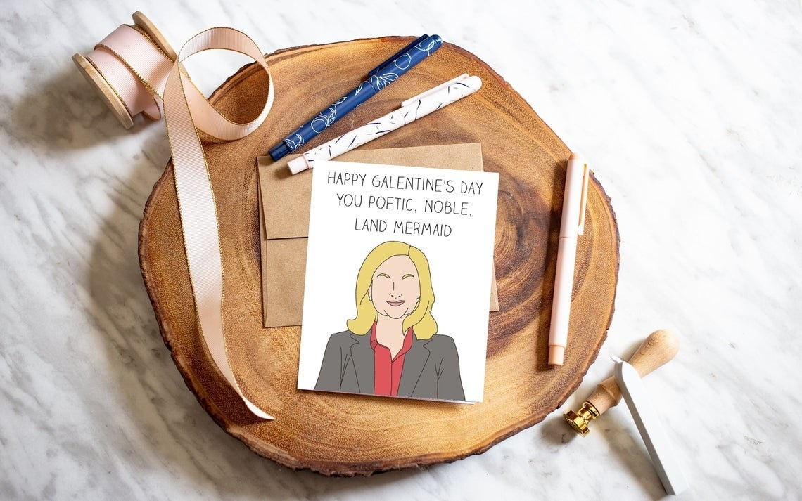 An greeting card on a wooden tray with a few pens beside it