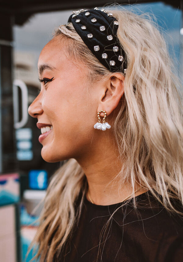 A person wearing the earrings and a headband