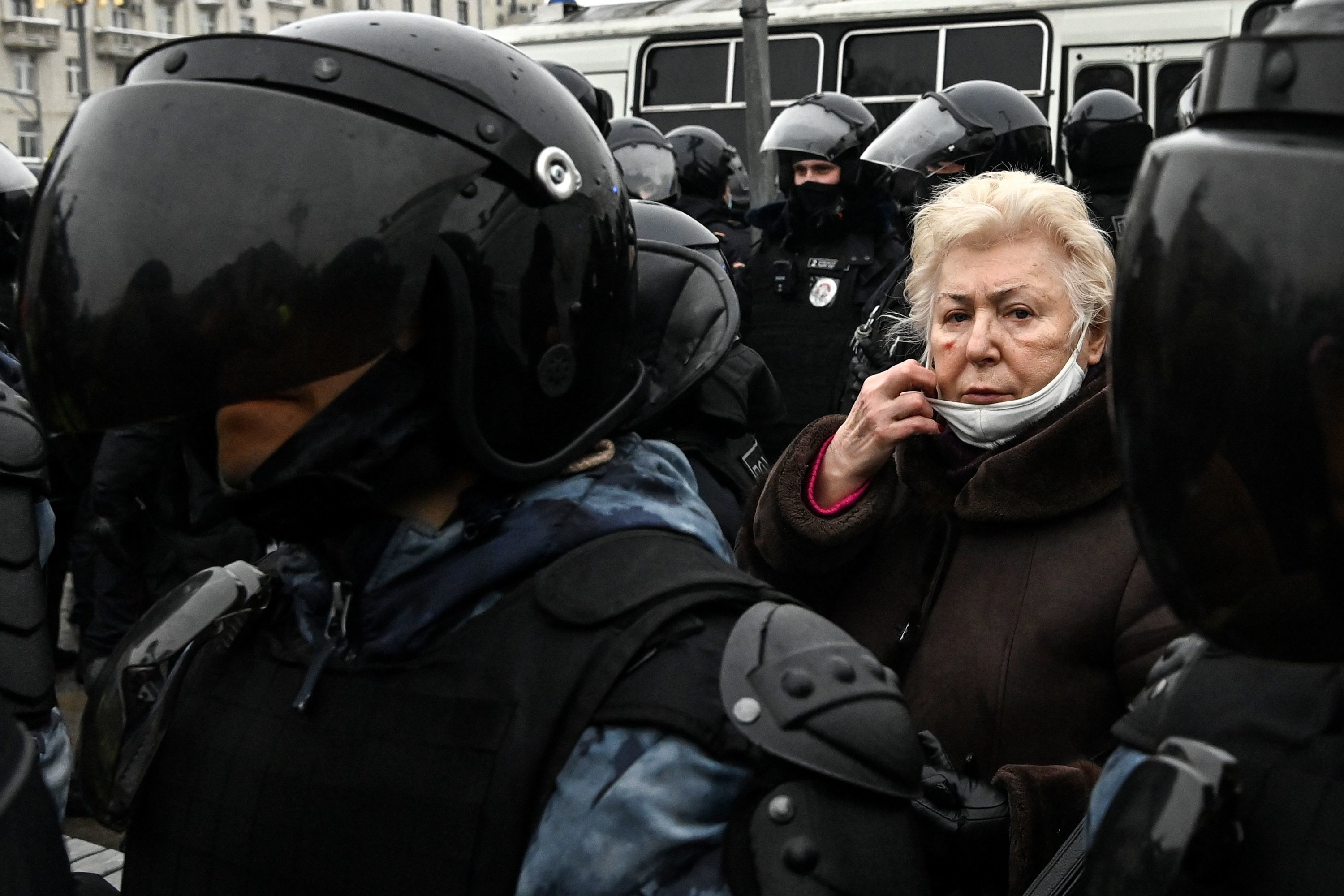 An elderly woman surrounded by police officers at a pro-Democracy rally in Russia