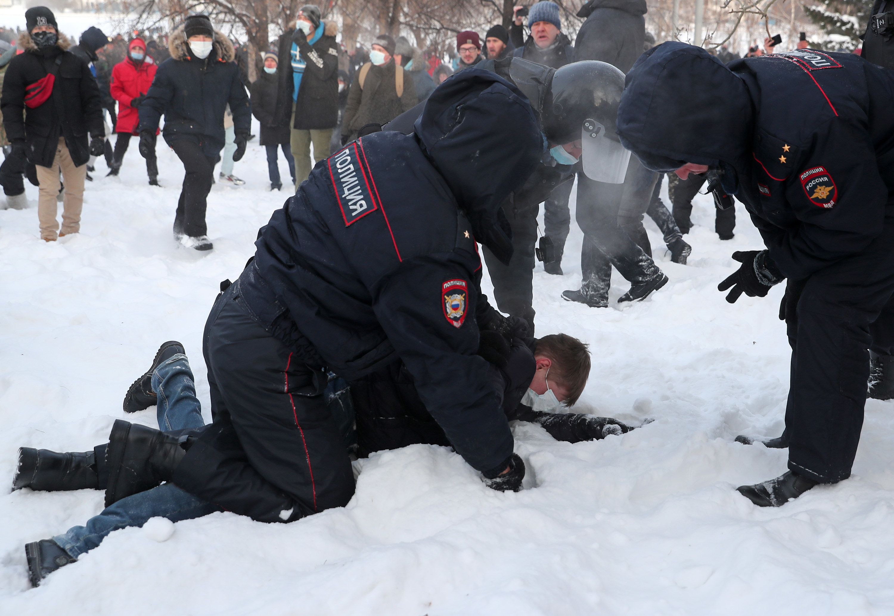 Police officers in uniform hold a man wearing a face mask down on the ground in the snow