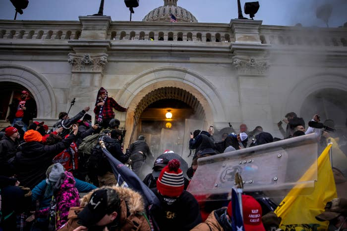 A group of people, some wearing Trump regalia, clash with police on the steps of the Capitol building