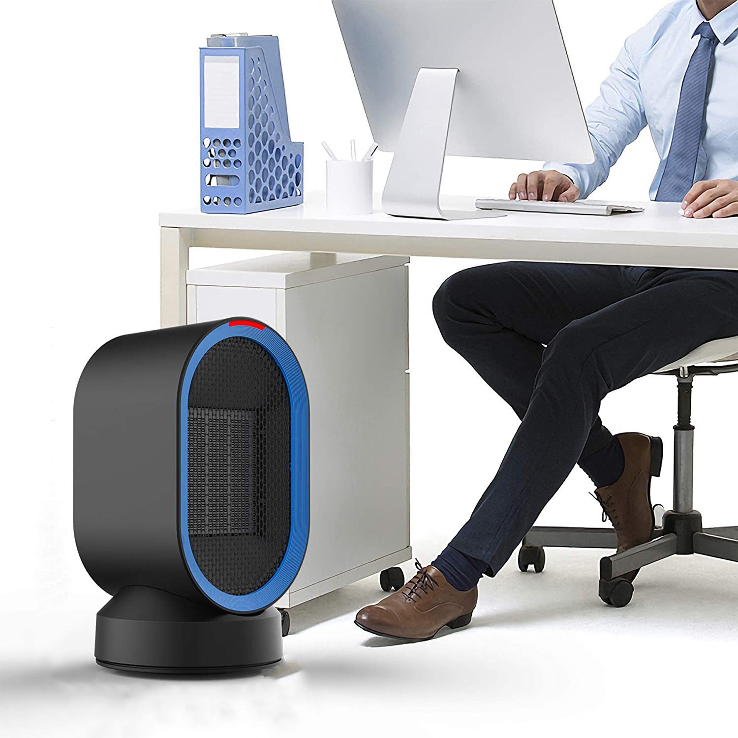 A person sitting at a desk with a small space heater at their feet
